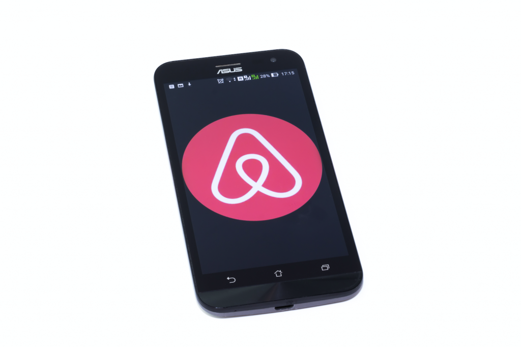 A phone displaying the Airbnb logo.